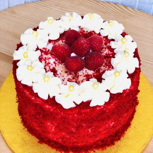 Gourmet red velvet celebration cake topped with fresh strawberries and icing flowers